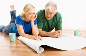 Middle-aged couple lying on floor looking at architectural blueprints together.
